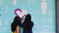 Estudiants de l'Institut Rubió i Ors decoren la porta del servei ''Renova i Repara'' de l'Hospitalet